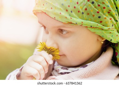 Little girl enjoys the smell of flowers on the yellow field (Recreation, summer, nature, vacation concept)