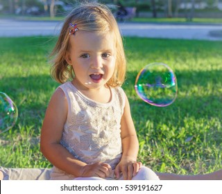 little girl enjoys soap bubbles.