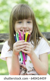 Little girl enjoys a sunny day in the park holding hands crayons