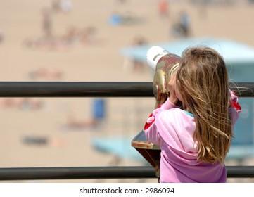 Little Girl Enjoys View of Beach Through Telescope