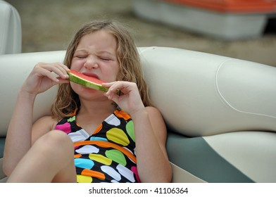a little girl enjoys a watermelon snack while on a boat