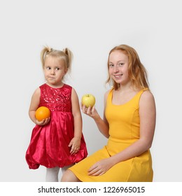 Little girl envies of the fruit to her older sister on gray background