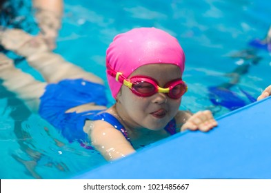 A little girl of European appearance in glasses in the pool, shows the language and looking at the camera