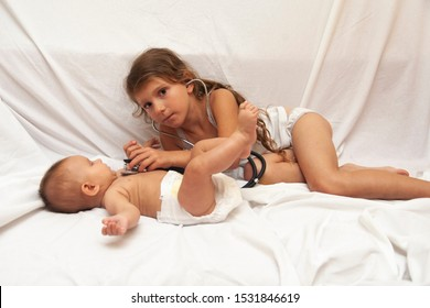 Little girl examines her baby sister by stethoscope. Doctor and patient.