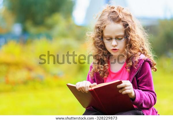 Kleines Mädchen in Brillen, das das Buch im Herbstpark liest. Bildungskonzept.