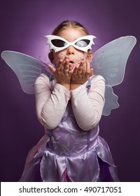 Little girl in fairy costume on a purple background