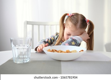 Little girl falling asleep at breakfast time. Theme of difficulty of children feed.