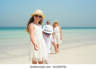 Little girl with family walking along a beach