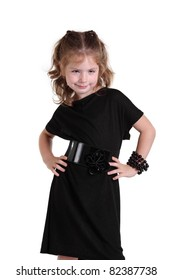 Little girl in a fashionable black dress on the white background