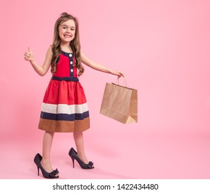 Little girl is a fashionista in dress and mom's shoes with a shopping bag , colored pink background , Studio shot , concept of children's fashion