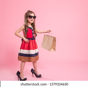 Little girl fashionista with glasses in a dress and mom's shoes with a shopping bag , on a colored pink background , Studio shooting , baby fashion concept