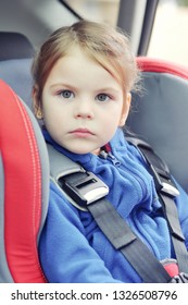 Little girl fastened with security belt in safety car seat.