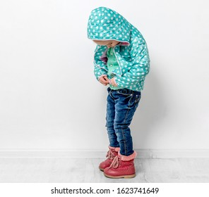 little girl fastening her blue dotted jacket