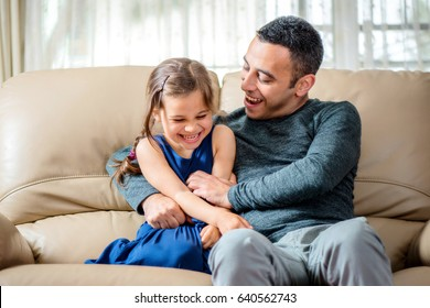Little Girl And Father Are Enjoying Being Together At Home
