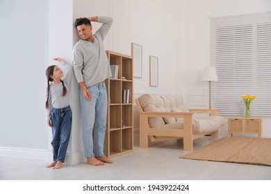 Little girl and father measuring their height near wall at home