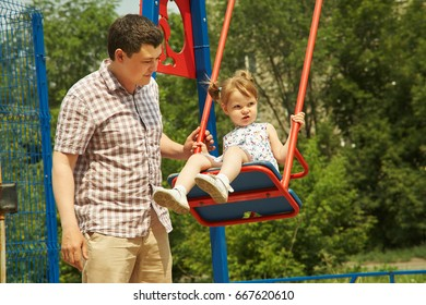 little girl with father on playground. playing child on swing