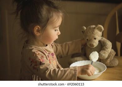 Little girl feed her teddy bear