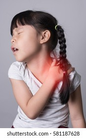 Little girl with felling pain touching her shoulder.Little girl suffers from shoulder pain.