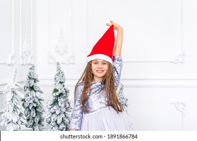 A little girl in a festive dress pulls herself by a red santa hat in a room with a Christmas decoration
