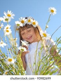 Little girl in field of beautiful summer flowers