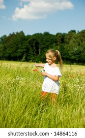 Little girl in a field making soap bubbles and having fun with it