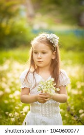 Little girl in a field with white small flowers in summer. Stellaria meadow