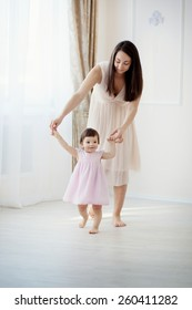 little girl first steps with the help of mom