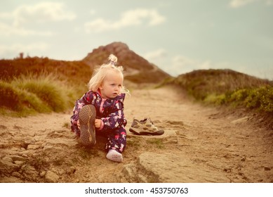 Little girl is fitting on mother's shoes on a path in the hills.