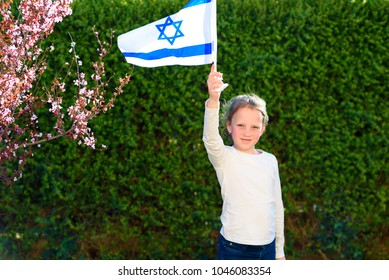 Little girl with the flag of israel.Patriotic holiday.