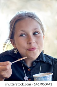 A little girl flashes a guilty look, as she gets caught eating ice cream before dinner. oops!