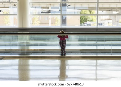 Little girl in floral print dress and pants standing on airport moving walkway