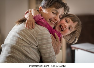 Little girl with flour on the face hugging with her smiling mother in home