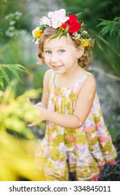Little girl in flower wreath in the garden