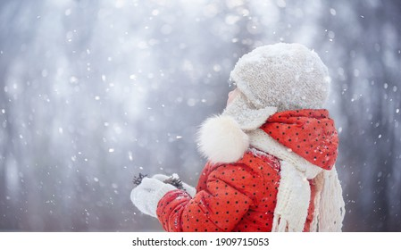a little girl in a fluffy hat walks on a snowy winter day