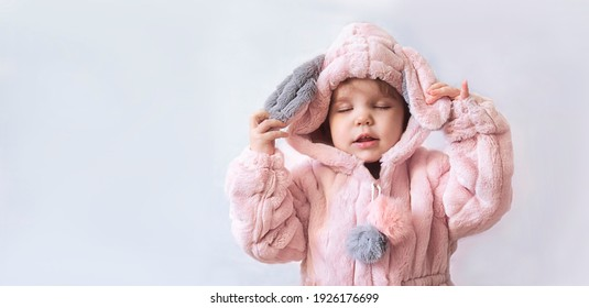 A little girl in a fluffy robe, kigurumi coat or fur coat closed her eyes and feels pleasant tenderness and comfort from pleasant sensations. Home clothes before bed and after bath. Copy space banner.