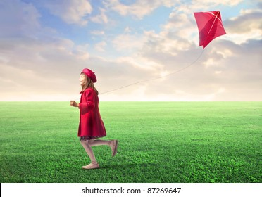 Little girl flying a kite on a green meadow
