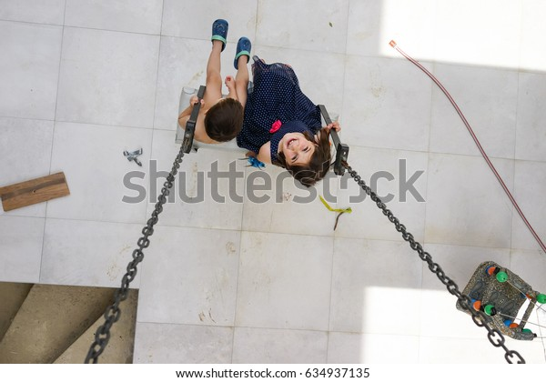 Little girl flying on swing in house yard. Childhood, Freedom, Happy, Summer, Outdoor
