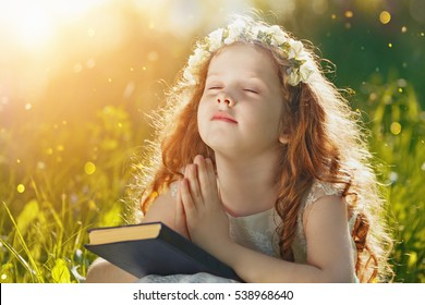 Little girl folded her hand and close your eyes in praying, dreaming in park outdoors.