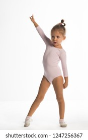 The little girl of four years is engaged in gymnastics on a white background