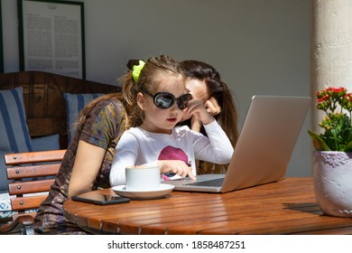 little girl four years old, holding sunglasses, touching with finger on laptop trackpad on brown wooden table, with woman