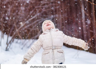 little girl four years on the street in winter white jacket catches snowflakes flakes and rejoices, smiles