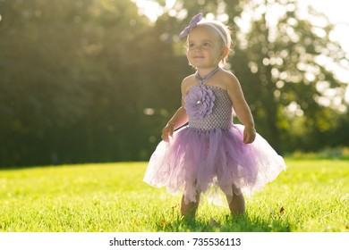 A little girl of fourteen months old on the grass