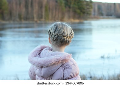 A little girl with franch milkmaid braid in her hair. Looking over a frozen river in winter.