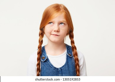 Little girl with freckles and braided in two long plaits red hair thinks, looks aside incredulously, with doubt, one corner of the lips pursed, white background, dressed in denim overall