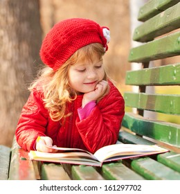 Little girl with freckles wearing a red reading a book on a bench in the park.