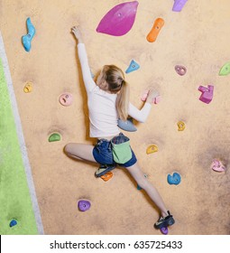Little girl free climbing on artificial wall in gym, bouldering.