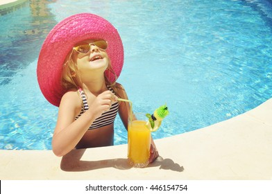 Little girl with fresh  cocktail on watter pool in the summer day
