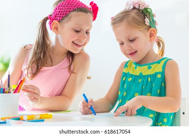 Little girl friends draw at the table together