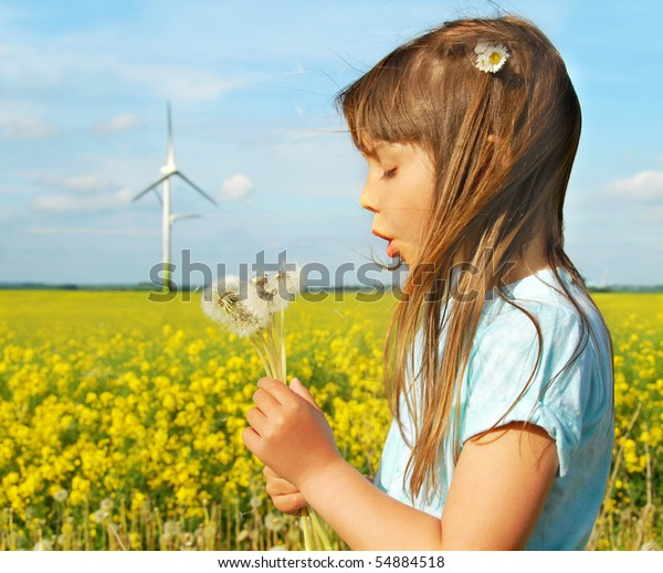 Little girl in front of windmills blowing dandelions