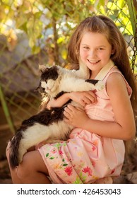 little girl in garden playing with the cat